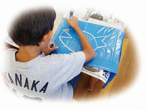 「佐賀の海」をテーマに、銀色のマーカーペンで絵を描いていく子どもたち